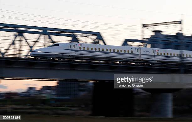 Central Japan Railway Co Shinkansen bullet train travels along an elevated railway track at dusk on January 19 2016 in Tokyo Japan Japanese...