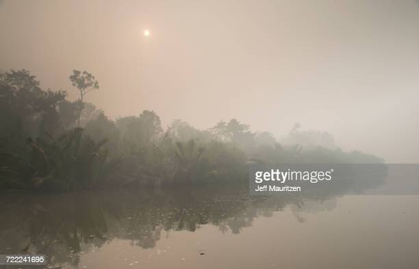 """""""Smoke from nearby forest fires obscures the sunrise over the Sekonyer river in Southern Borneo along the Tanjung Puting National Park, Indonesia."""""""