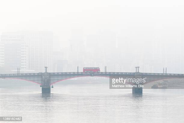 Central London City Skyline with iconic red London bus driving over Lambeth Bridge with misty foggy skyscraper buildings shot in Coronavirus Covid-19...