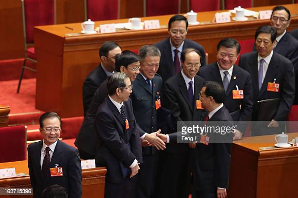 Central officials shake hands with China's newlyelected Premier Li Keqiang as former Premier Wen Jiabao leaving during the fifth plenary meeting of...