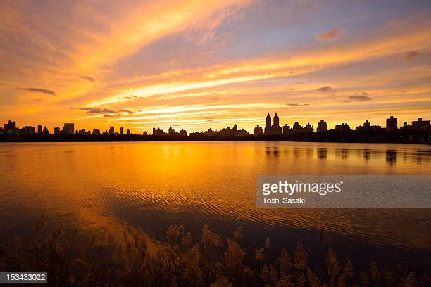 central park reservoir glowing  at sunset. - central park reservoir stock pictures, royalty-free photos & images