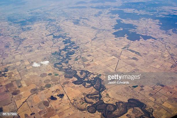 a river snakes its way through drought-stricken farmland in summer. - drought stock pictures, royalty-free photos & images