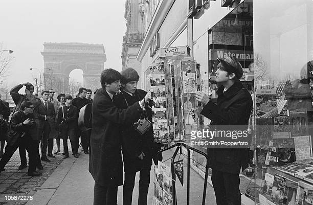 Paul McCartney George Harrison and John Lennon of The Beatles looking at a postcard display on the ChampsElysees Paris 1964 The group are performing...