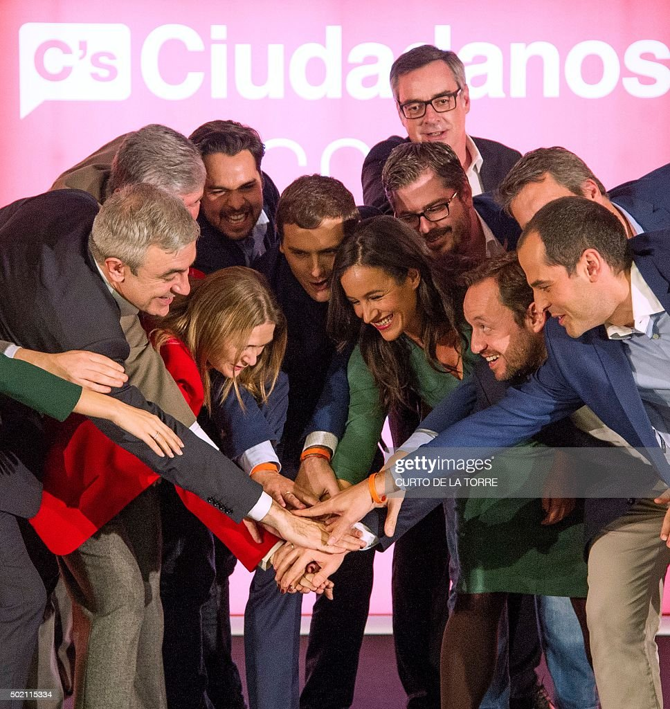 Centre-right party Ciudadanos leader and candidate for the general election, Albert Rivera (C) holds hands with other party members after the results of Spain's general election in Madrid on December 20, 2015. Spain's ruling conservative Popular Party won the most seats in parliament in a general election today but lost its absolute majority, partial results showed with over 80 percent of votes counted.