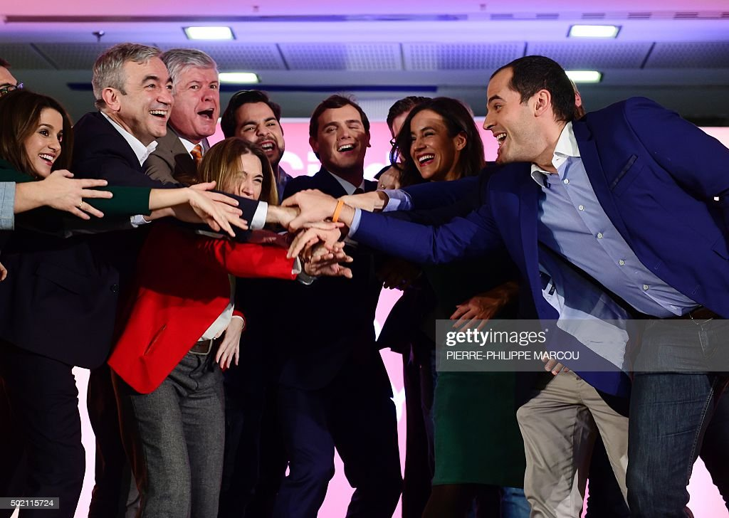 Centre-right party Ciudadanos leader and candidate for the general election, Albert Rivera (C) holds hands with other members of the party, after the results of Spain's general election in Madrid on December 20, 2015. Spain's ruling conservative Popular Party won the most seats in parliament in a general election today but lost its absolute majority, partial results showed with over 80 percent of votes counted.