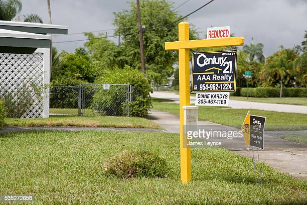 A Century 21 for sale sign reading that the price has been reduced stands outside a house in Hollywood Florida