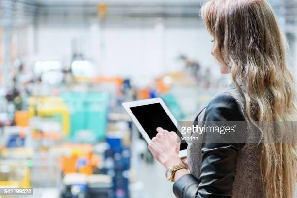 Ceo using tablet at factory
