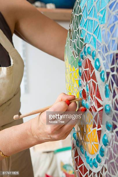 ceramic artist working on a piece in her studio - mosaic stock photos and pictures