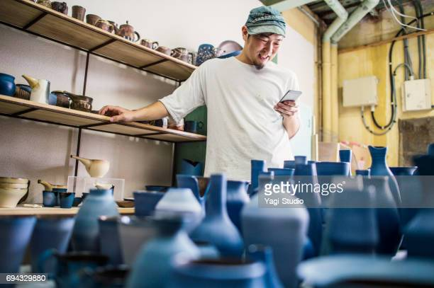 Ceramic artists using smart phone at studio