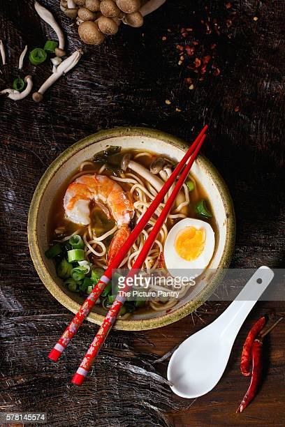 Ceramic bowl of asian ramen soup with shrimp, noodles, spring onion, sliced egg and mushrooms, served with red chopsticks