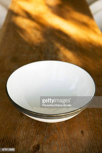 Ceramic bowl with metal rim on wooden table