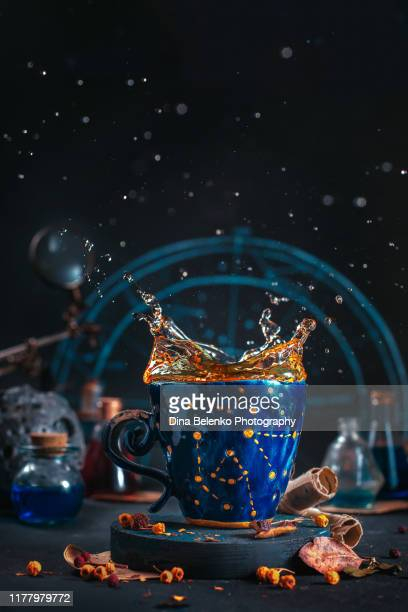 ceramic cup with golden stars and a tea splash, autumn still life with leaves, berries and tea on a dark background and copy space - khabarovsk krai stock pictures, royalty-free photos & images