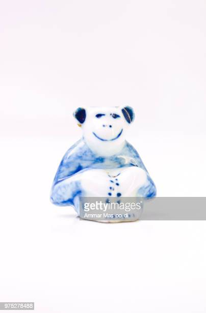 a ceramic doll of light blue monkey isolated on white background - bringing home the bacon stock photos and pictures