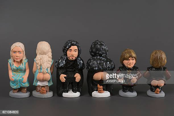 Ceramic figurines called 'caganers' representing Daenerys Targaryen Jon Snow and Tyrion Lannister from Game of Thrones are displayed at a factory in...