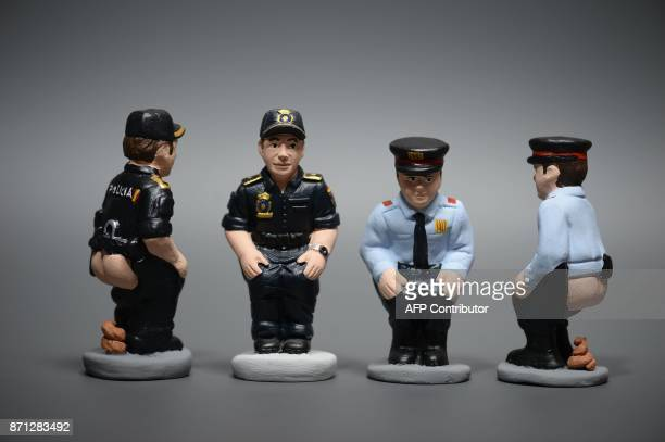 Ceramic figurines called 'caganers' representing Spanish national policemen Catalan regional policemen are displayed at a factory in Torroella de...