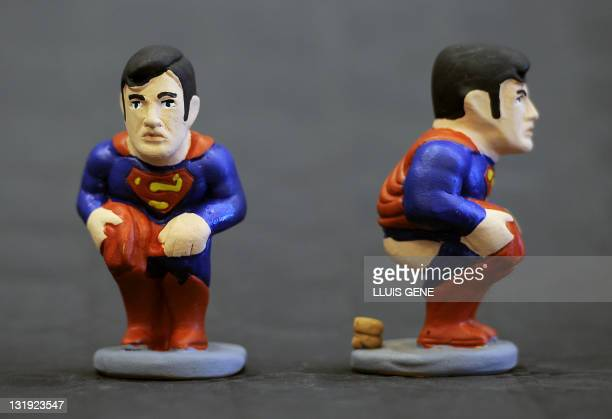 Ceramic figurines known locally as caganers of cartoon character Superman are displayed on November 8 2011 Statuettes of wellknown people defecating...