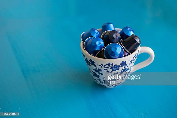Ceramic mug filled with coffee capsules