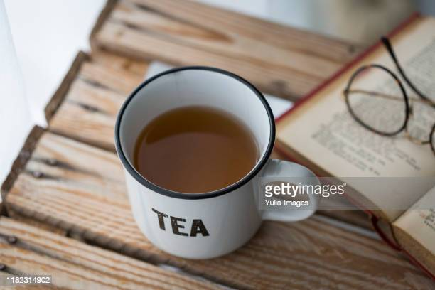ceramic mug with the word tea alongside a book - steeping stock pictures, royalty-free photos & images