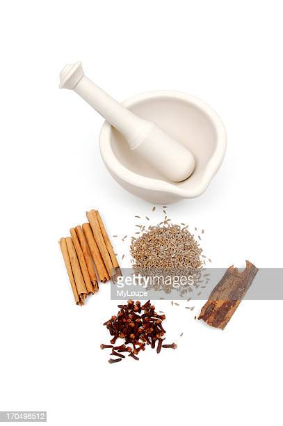 Ceramic Pestle And Mortar With Spices Like Cinnamon Sticks Cumin Seeds Cloves And Cinnamon Bark In Front