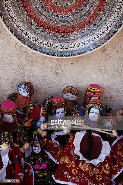 Ceramic plate, hand fired and painted with traditional designs, is displayed with handmade dolls in regional costume. Avanos, Turkey.