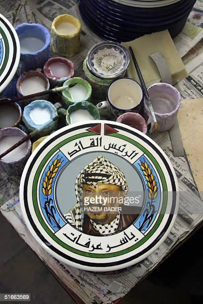 A ceramic plate with a portrait of Palestinian leader Yasser Arafat is displayed at a painter's workshop in the West Bank city of Hebron 04 November...