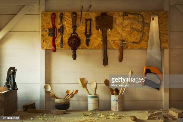 ceramic pots with a selection of finished handmade wooden spoons and hand tools for carving and cutting wood hanging on a toolboard on a wall above the workbench in a craftsmans workshop. - carving craft product stock pictures, royalty-free photos & images