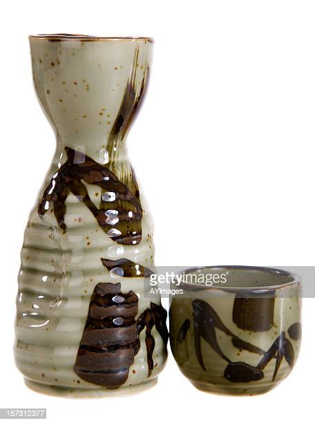 Pichet et verre de saké en céramique sur fond blanc