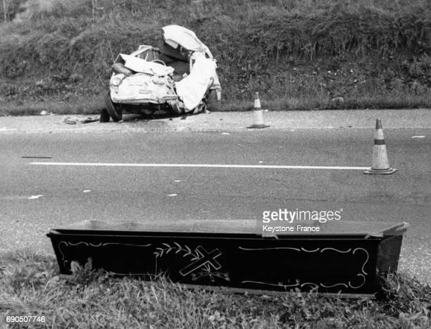 Cercueil posé que le bord de la chaussée de l'autoroute MilanBergame face à l'épave d'une des voitures accidentées en Italie le 5 octobre 1963