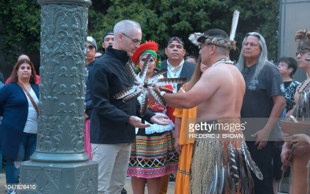A ceremonial running staff is given by Kevin Nunez dressed in tradional costume of his Native American Tongva tribe to Los Angeles City Council...