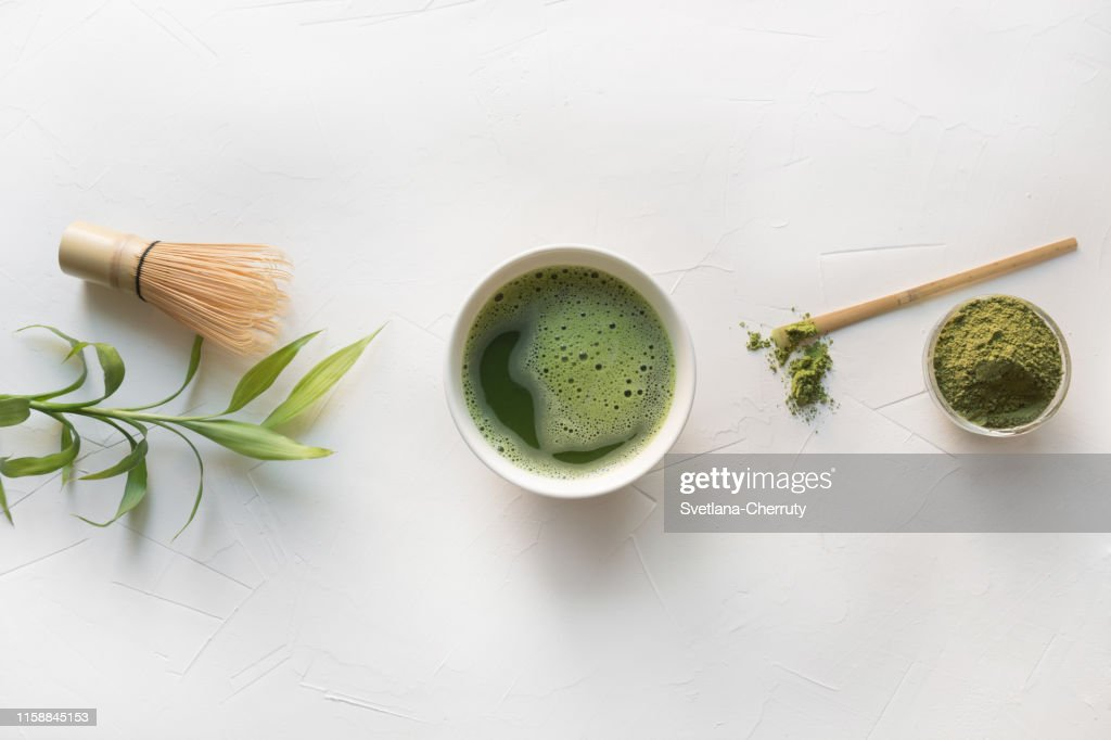 Ceremony green matcha tea and bamboo whisk on white concrete table. Top view. : Stock Photo