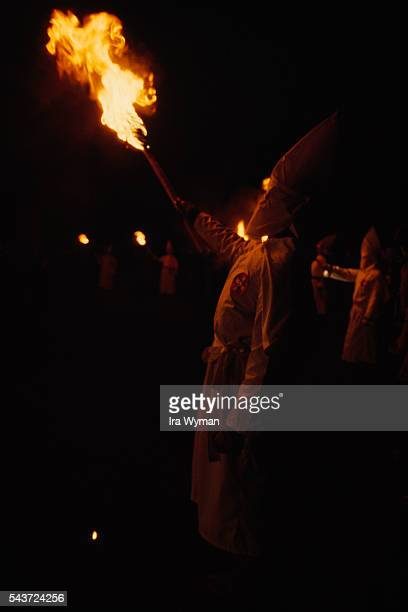 Ceremony of Ku Klux Klan a secret militant organization advocating white supremacy and acts of terrorism while hiding behind conical hats masks and...