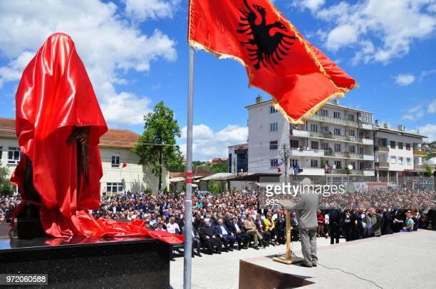 ceremony uncovered monument adem jashari in the town square in dragash - bandiera albanese foto e immagini stock