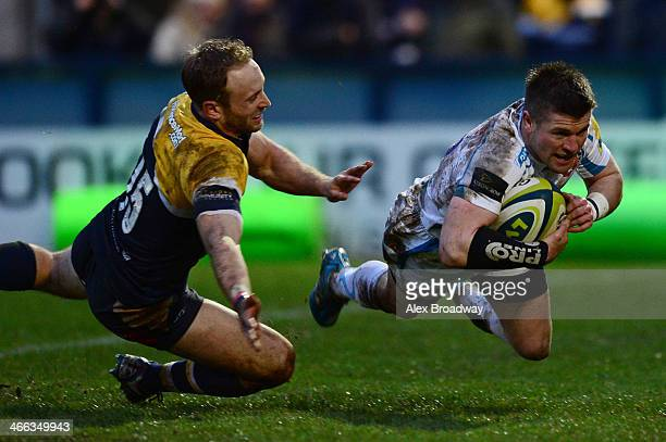 Ceri Sweeney of Exeter Chiefs dives past Chris Pennell of Worcester Warriors to score a try during the LV= Cup match between Worcester Warriors and...
