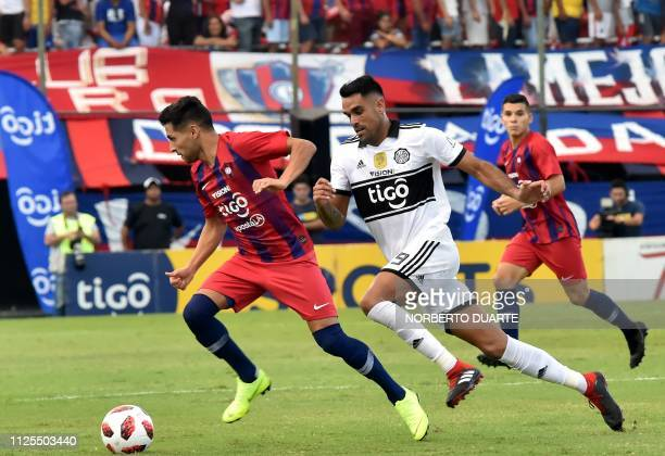 Cerro Porteno's Argentine Federico Carrizo is challenged by Olimpia' Carlos Rolon during the Paraguayan Apertura football tournament derby at the...