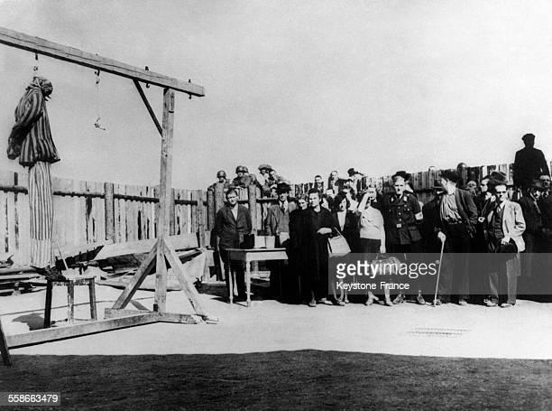 Certains habitants de Weimar amenés au camp de Buchenwald par la police militaire américaine détournent la tête pour ne pas voir la potence à...