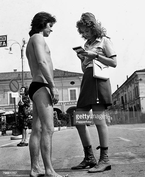 Cervia Italy 17th July 1973 A Policewoman 'books' a man for wearing a bathing costume on the street where there is a law against the wearing of...