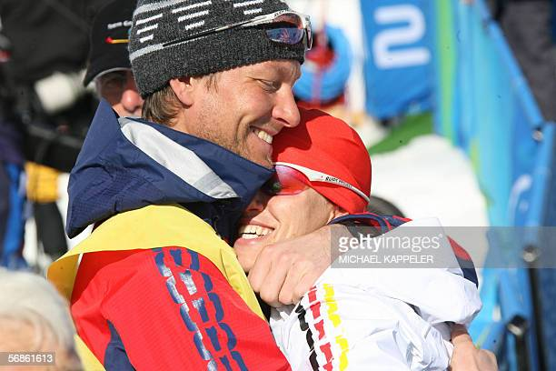 Germany's double Olympic champion Kati Wilhelm is consoled by her boyfriend Andreas Emslander after she came in seventh during the 75km sprint of the...