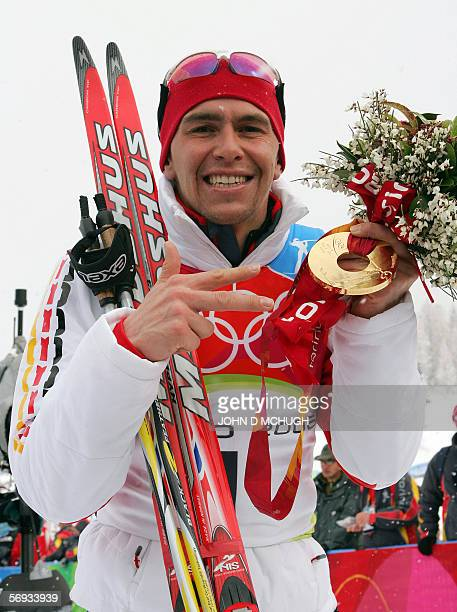 Germany's Michael Greis holds up the gold medal he won in the men's biathlon mass start as he indicates the number three for the total number of...