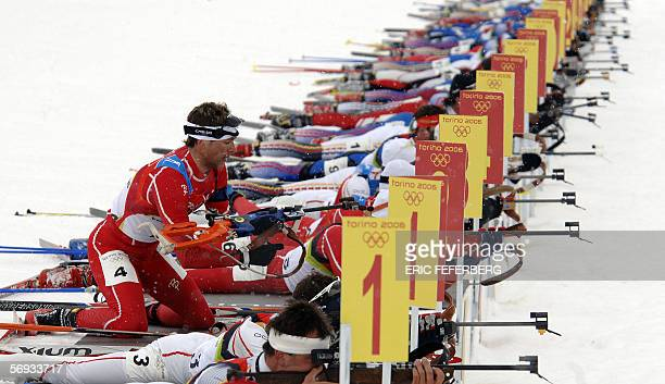 Cesana San Sicario, ITALY: Norway's Ole Einar Bjoerndalen takes his position with competitors at the shooting range in the men's biathlon 15km mass...