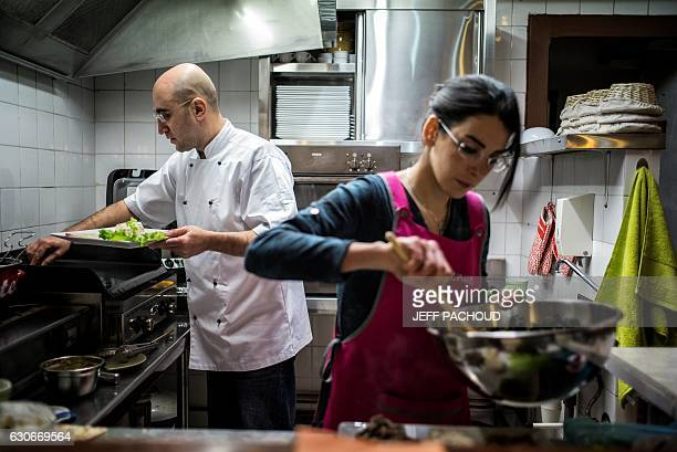 Cesar Asfar and his wife Rima refugees from Syria and restaurant owners work in the kitchen of their restaurant 'Delices D'Alep' in Tournus eastern...