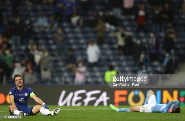 Cesar Azpilicueta of Chelsea celebrates following their side's victory as Phil Foden of Manchester City looks dejected after the UEFA Champions...