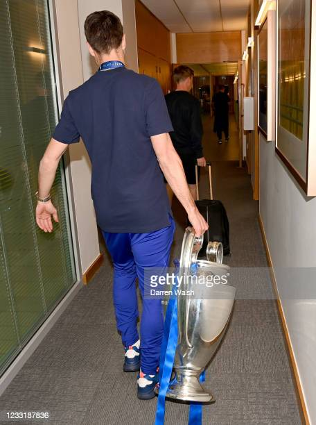 Cesar Azpilicueta of Chelsea holds the trophy as they arrive back at the Chelsea Training Ground following yesterday's victory in the UEFA Champions...