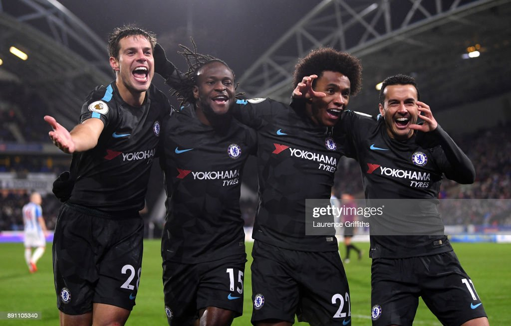 Cesar Azpilicueta, Victor Moses, Willian, and Pedro of Chelsea celebrate Pedro's goal during the Premier League match between Huddersfield Town and Chelsea at John Smith's Stadium on December 12, 2017 in Huddersfield, England.