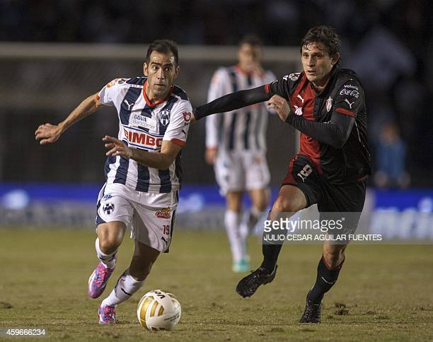 Cesar Delgado of Monterrey and Luis Caballero of Atlas during a quarterfinal football match of 2014 Mexican Apertura tournament football match in...