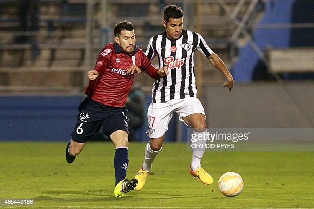 Cesar Fuentes of Chile's Universidad Catolica vies for the ball with Jorge Gonzalez of Paraguay's Libertad during their Copa Sudamericana football...