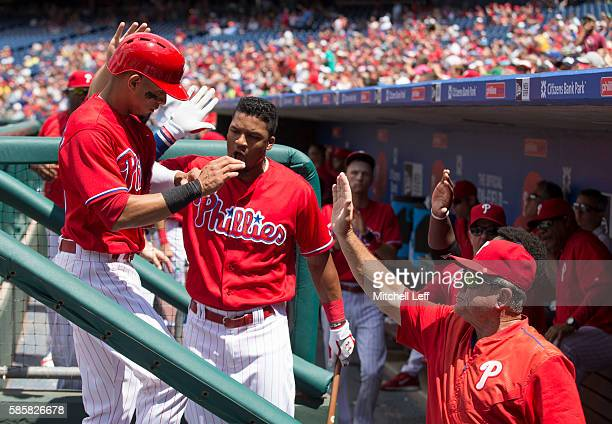 Cesar Hernandez of the Philadelphia Phillies high fives Jimmy Paredes and Larry Bowa after scoring a run in the bottom of the first inning against...