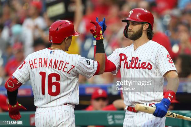 Cesar Hernandez of the Philadelphia Phillies is congratulated by Bryce Harper after he hit a home run against the Miami Marlins during the first...