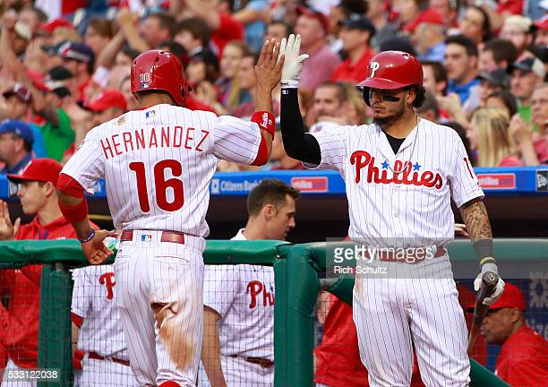 Cesar Hernandez of the Philadelphia Phillies is congratulated by teammate Freddy Galvis after scoring on a ball hit by Ryan Howard against the...