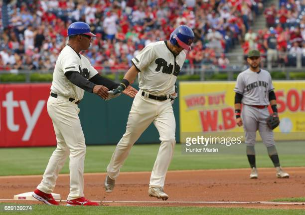 Cesar Hernandez of the Philadelphia Phillies is congratulated by third base coach Juan Samuel after hitting a home run in the first inning during a...