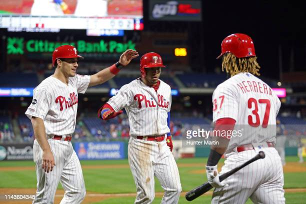 Cesar Hernandez of the Philadelphia Phillies is greeted at the dugout by JT Realmuto and Odubel Herrera after hitting a tworun home run in the fifth...